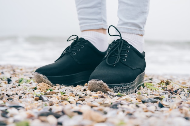 Jambes féminines en chaussures noires et jeans