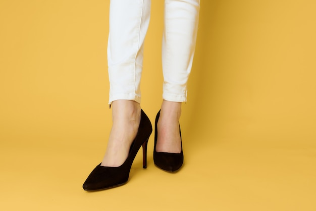 Jambes féminines chaussures noires mode look attrayant jeans blancs jaune
