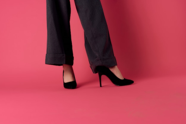 Jambes féminines en chaussures noires posant un style moderne de fond rose