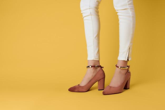 Jambes féminines en chaussures pantalons blancs posant fond isolé libre
