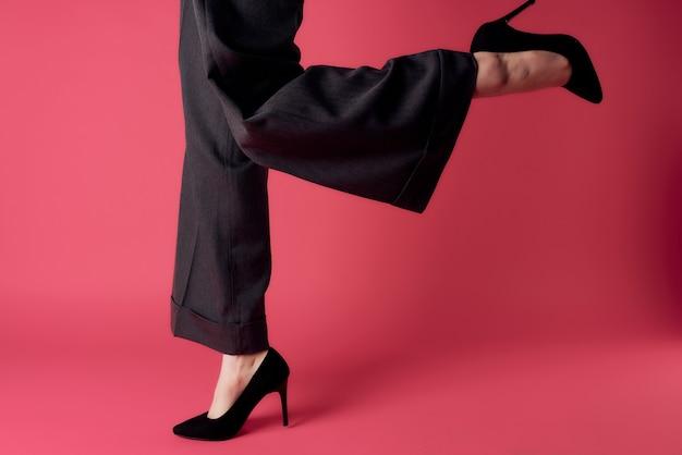 Jambes féminines en chaussures pantalons noirs posant une mode de style élégant