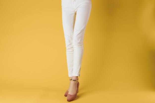 Jambes féminines en chaussures recadrée vue posant l'été de la mode