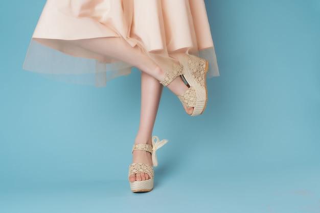 Jambes féminines en chaussures robe posant fond bleu fashion