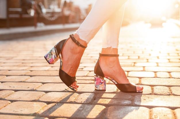 Jambes féminines en chaussures à talons hauts d'été de mode en jeans blancs sur le fond d'un coucher de soleil lumineux. fermer.