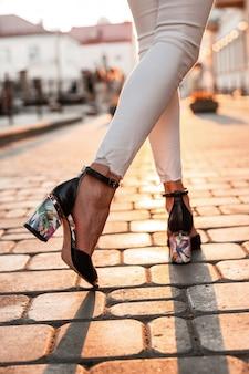 Jambes féminines en chaussures à talons hauts d'été de mode en jeans blancs sur le fond d'un coucher de soleil lumineux. vue de dessus