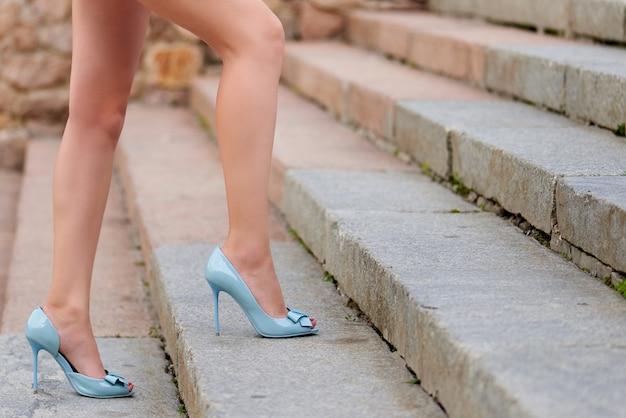 Jambes féminines sur des chaussures à talons hauts sur les marches.