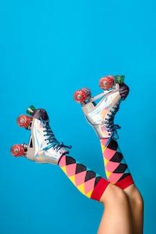 Jambes féminines dans des chaussures de patins à roulettes avec fond bleu