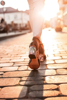 Jambes féminines dans des chaussures à talons hauts d'été élégantes en jeans blancs sur fond d'un coucher de soleil lumineux. vue de dessus