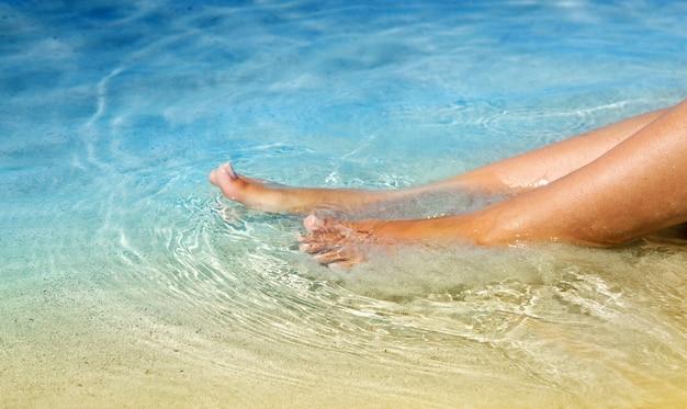 Jambes féminines dans l'eau cristalline