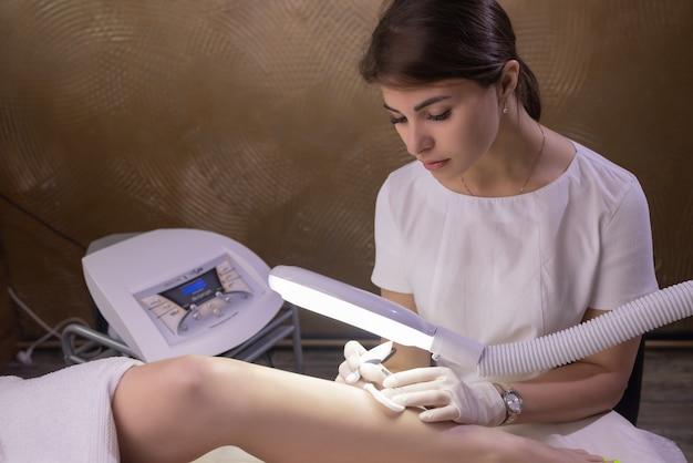 Jambes féminines sur drap violet pendant l'épilation par une esthéticienne professionnelle en gants. spa, industrie de la beauté, traitement en clinique, électrolyse.