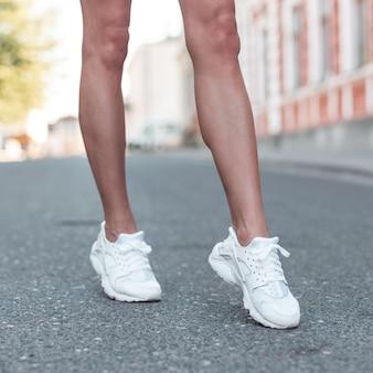 Jambes féminines élancées sportives dans des baskets blanches à la mode. fille se promène dans la ville sur l'asphalte. gros plan des jambes bronzées féminines dans des chaussures élégantes.
