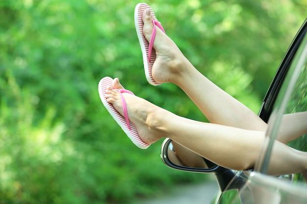 Jambes féminines sur la fenêtre de la voiture sur la nature