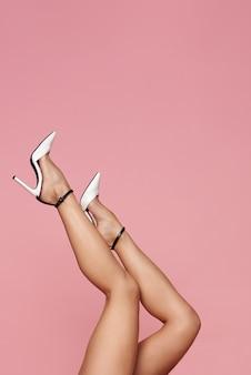 Jambes féminines sur de hauts talons blancs sur fond rose
