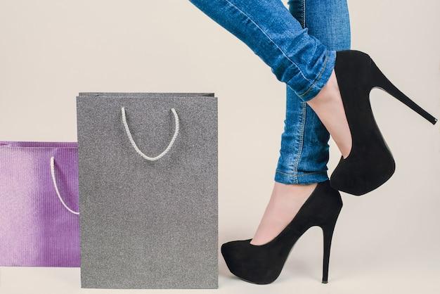 Jambes féminines en highheels debout près de sacs en papier fond blanc isolé avec copyspace