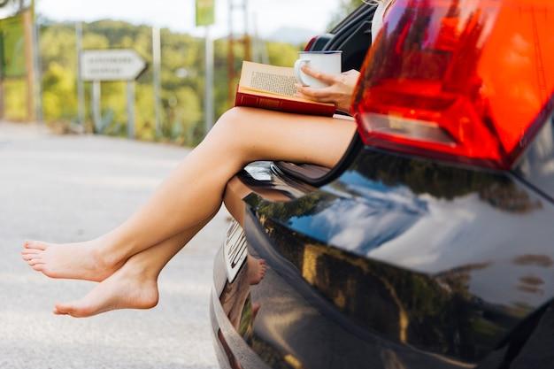 Jambes féminines hors du coffre de la voiture