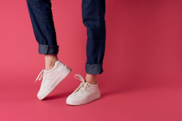 Jambes féminines inversées en baskets blanches sur fond rose vue recadrée studio. photo de haute qualité