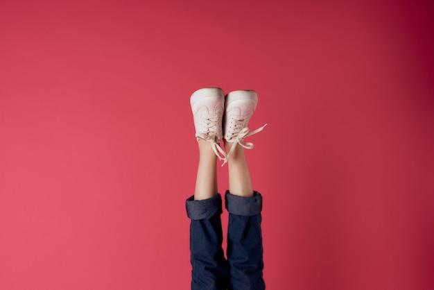 Jambes féminines inversées avec des baskets blanches sur fond rouge