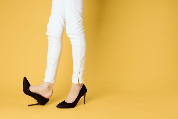 Jambes féminines inversées en chaussures noires posant sur fond jaune