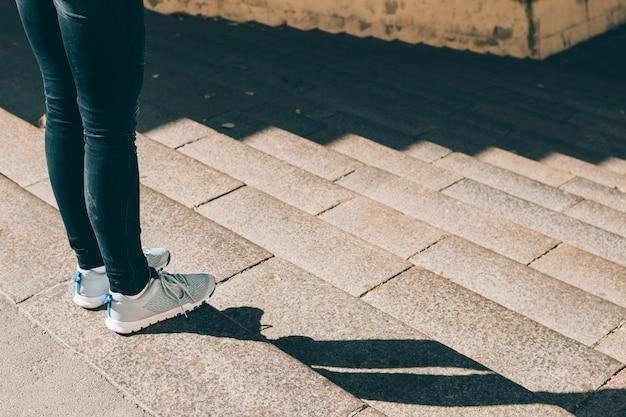 Jambes féminines en jeans et baskets