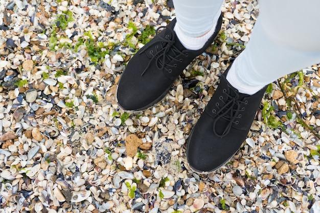 Jambes féminines en jeans et chaussures debout sur le rivage de coquillages