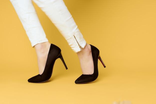 Jambes féminines en mode chaussures noires posant de luxe