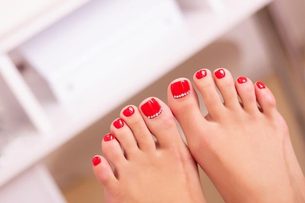 Jambes féminines avec des ongles de pédicure, vernis gel rouge