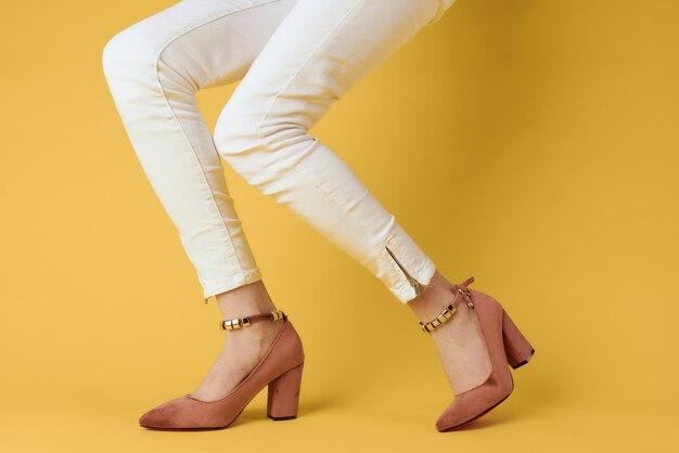 Jambes féminines pantalon blanc vêtements à la mode chaussures luxe jaune