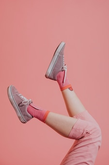 Jambes féminines en pantalon rose en l'air