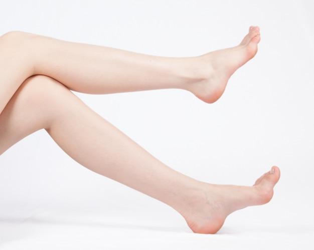 Jambes féminines parfaites, isolés sur fond blanc