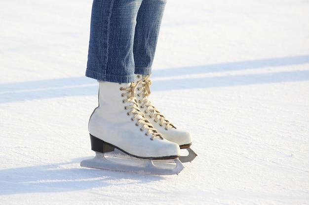 Jambes féminines en patins sur une patinoire