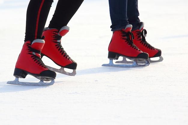 Jambes féminines en patins sur la patinoire