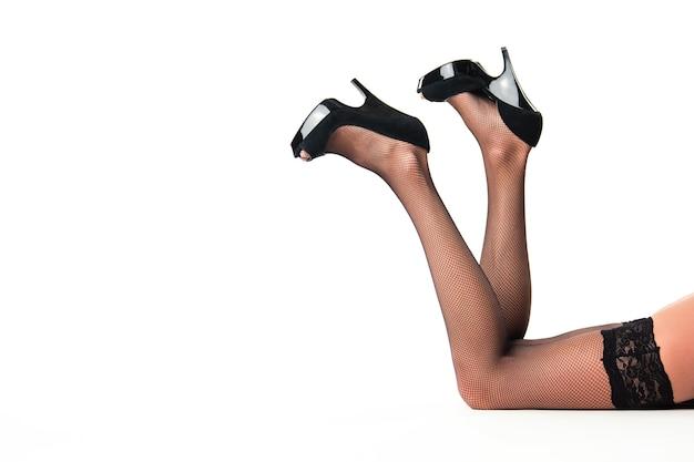 Jambes féminines portant des talons. chaussures à talons et bas noirs. insistez sur la sexualité. soyez belle et féminine.