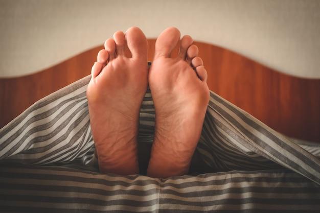 Jambes féminines sous le drap. la plante des pieds d'une jeune femme allongée dans son lit sous une couverture à rayures