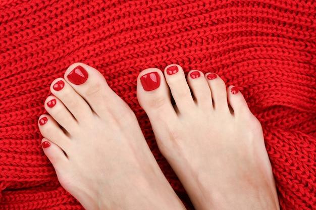 Jambes féminines sur un tissu rouge. pieds réchauffés