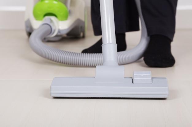 Jambes de femme avec aspirateur nettoyage plancher