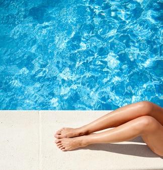 Jambes de femme au bord de la piscine