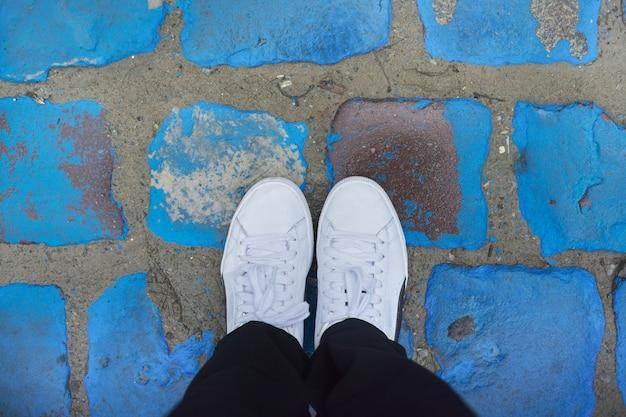 Jambes de femme en baskets blanches sur des pavés peints en bleu vintage