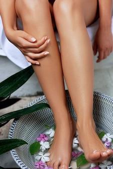Jambes de femme de beauté. traitement et produit de spa pour les pieds de femme