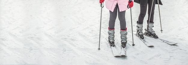 Jambes de femme en chaussures de ski sur le paysage enneigé avec fond, planche de ski, vacances de voyage pour la bannière.