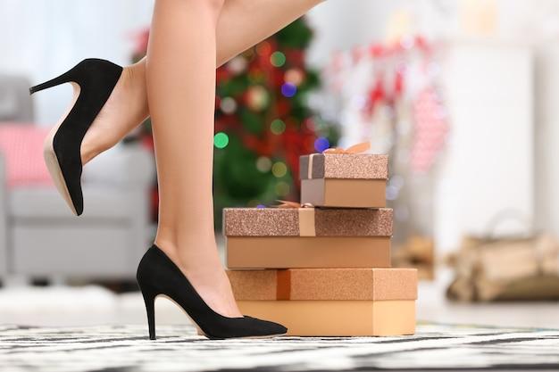 Jambes de femme en chaussures à talons hauts et coffrets cadeaux à la maison