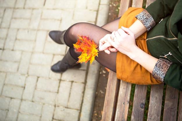 Jambes d'une femme en collants de nylon dans une pose fermée jambe sur jambe dans une mini jupe moutarde courte et dans une veste verte avec une feuille d'érable à la main. promenade d'automne sur un banc de parc. ambiance et mode d'automne