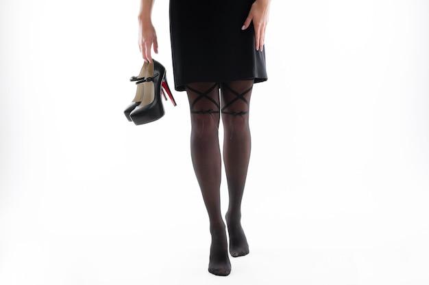 Jambes d'une femme en collants avec des talons hauts