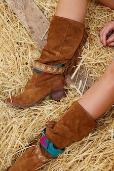 Jambes de femme avec cuir marron sur ballot de paille