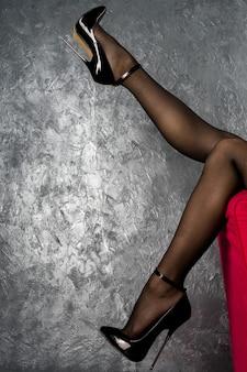 Jambes de femme en cuir verni brillant noir talons aiguilles avec bride à la cheville près du mur de stuc vénitien