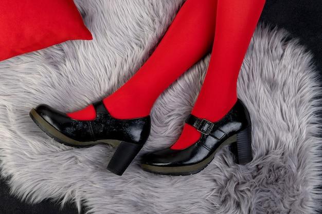 Les jambes de la femme dans des chaussures à la mode sur une surface velue grise