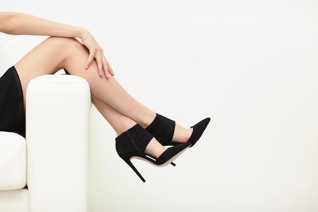Jambes de femme dans des chaussures noires élégantes sur un mur blanc avec espace de copie