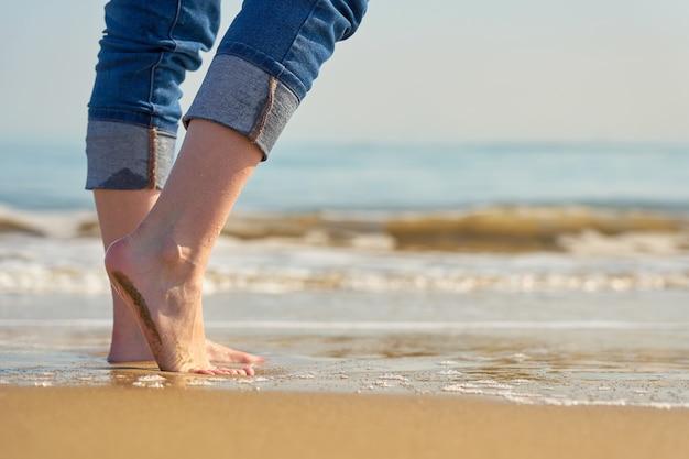 Jambes d'une femme dans l'eau sur une plage de sable tropicale avec vagues et horizon