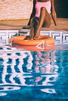 Jambes de femme dans une piscine avec bouée de sauvetage