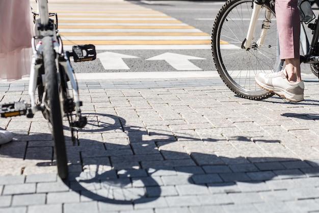 Jambes de femme debout près de vélo et jambes d'homme à vélo sur le carrelage du trottoir en face de la route transversale