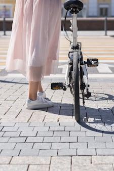 Jambes de femme debout près de vélo à vélo sur carrelage de trottoir en face de la verticale de la route transversale